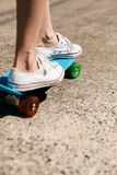 Young girl in sneakers on skateboard. Royalty Free Stock Photography