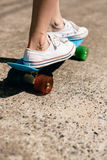 Young girl in sneakers on skateboard. Royalty Free Stock Images