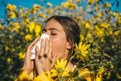 Young girl sneezing and holding paper tissue in one hand and flower bouquet in other. Young woman got nose allergy, flu royalty free stock photo