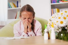 Young girl sneezing at home with paper towel prepared to blow he Stock Images