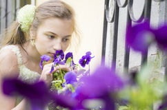 Young girl sniffing beautifull flowers. Young girl sniffing beautifull blue flowers near window grill Stock Photography