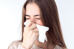 Young girl with sniffles wipes the nose closeup. In studio Stock Images