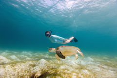 Young girl snorkeling with sea turtle Stock Photo
