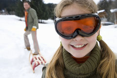 Young girl in snow goggles with father pulling sled in background Stock Images