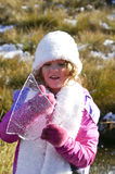 Young Girl in Snow Holding a Sheet of Ice From Lake. Young girl dressed in warm clothes, beanie, gloves and scarf holding a sheet of ice from a frozen lake Royalty Free Stock Images