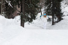 Young girl snowboarder goes towards camera on snowy mountain in the forest Stock Images
