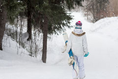 Young girl snowboarder going down on a snowy mountain in the forest Stock Images