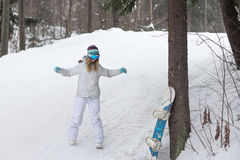 Young girl snowboarder warming up before a descent from the mountain Royalty Free Stock Photo