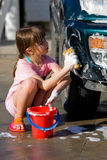 Young Girl with Soap Suds Carwash. Young girl cleans car for pocket money, makes game of it. Handwashing car to save water and earn pocket money royalty free stock image