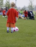 Young girl soccer player. Here is a picture of a young girl with a soccer ball, waiting to get on the field and play Royalty Free Stock Photography