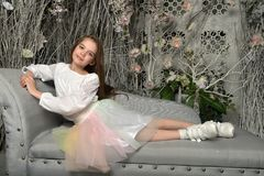 Young girl on the sofa. In a dreamlike interior Royalty Free Stock Images