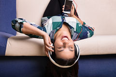 Young girl on a sofa enjoying her music Stock Images