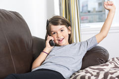 Young girl in a sofa. A Young girl in a sofa  with phone Royalty Free Stock Image