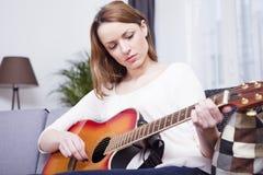 Young girl on sofa playing guitar Stock Image