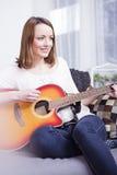 Young girl on sofa playing guitar Royalty Free Stock Photo