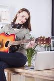 Young girl on sofa playing guitar Stock Photo