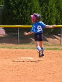 Young Girl Softball Player Running. A young girl who is suspended in air while running to base during a softball game. 7 years old stock photos