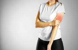 A young girl sore arm. The pain in my arm. The pain is marked in. Red. Isolated on grey background royalty free stock photography