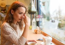 Crying young woman in cafeteria Stock Photography