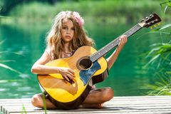 Young girl with spanish guitar on jetty. royalty free stock photography