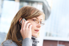 The young girl speak by mobile phone. The young girl in glasses., talks by a mobile phone. The person close up royalty free stock image