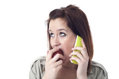Young girl speaking on the phone and eating an apple Royalty Free Stock Photos