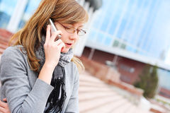 The young girl speaks by mobile  phone. Business Royalty Free Stock Images