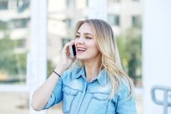 Young girl speaks on the phone in the street. Concept of life style, urban, work. royalty free stock images