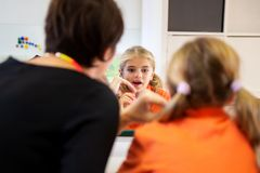 Young girl in speech therapy office. Mirror reflection of young girl exercising correct pronunciation with speech therapist. royalty free stock photos