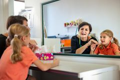 Young girl in speech therapy office. Mirror reflection of young girl exercising correct pronunciation with speech therapist. royalty free stock photography