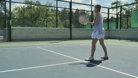 Young girl spend her leisure time at the tennis court outdoors stock video footage