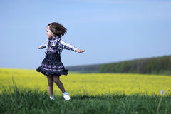 Young girl spinning. Young cute child dancing and spinning  in nature near yellow canola field Stock Image