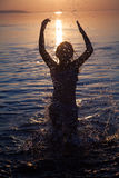 Young girl splashes water at sunset Royalty Free Stock Photography