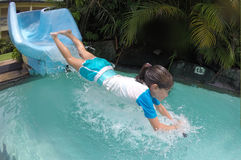 Young girl splashing into pool after going down water slide Royalty Free Stock Photo