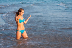 Young girl splashing on the sea Stock Photography