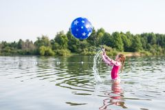 Young girl splashing and throwing ball in lake stock images