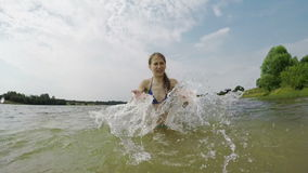 Young girl splashing the water in the lake stock footage