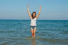 Young girl splashing the water in the sea Stock Photos