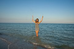 Young girl splashing the water in the sea Stock Photography