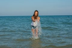 Young girl splashing the water in the sea Royalty Free Stock Image