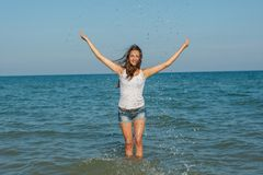 Young girl splashing the water in the sea Stock Photo