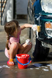 Young Girl with Sponge Cleaning Car. Young girl cleans car for pocket money, makes game of it. Handwashing car to save water and earn pocket money stock photography