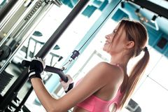 Young girl in sport gloves in gym healthy lifestyle exercising on cable machine holding bar looking aside cheerful back. Young woman wearing sport gloves in gym stock photo