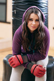 Young girl in sport wear, sitting on punching bag Royalty Free Stock Images