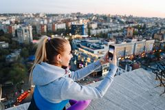 Young girl in sports uniform takes photos on the phone on the roof of a building over the city stock photo