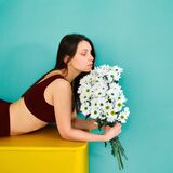 A young girl in sportswear is lying on a yellow chest of drawers with flowers in her hands