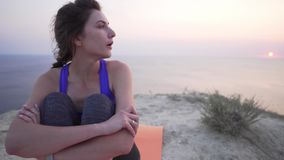 Young girl in sportswear is tired, sitting on a rock and watching the sunset after training. 4k stock video footage