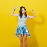 Young girl spreading hands isolated on yellow background royalty free stock image