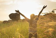 Young girl spreading hands with joy and inspiration. Facing the sun Royalty Free Stock Photo