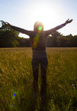 Young girl spreading hands with joy and inspiration facing the sun,sun greeting. Young girl spreading hands with joy and inspiration facing the sun,sun Stock Images